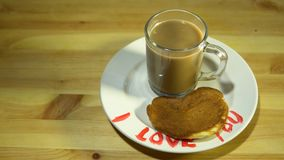 A plate with pancakes in the form of a heart and a mug with coffee on a table. A cup of hot coffee stands on a white plate with a red inscription I love you stock video footage