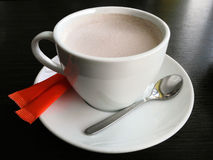 Cup of hot coffee with sugar. And spoon at table Royalty Free Stock Photos