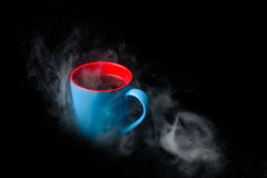 Cup of hot coffee surrounded in steam black background Stock Photo