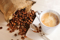 Cup of hot coffee on table and sack with coffee beans closeup Stock Photos
