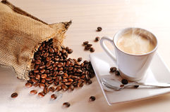 Cup of hot coffee on table and sack with coffee beans Stock Photos