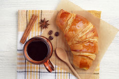 Cup of hot coffee and tasty croissant Royalty Free Stock Image