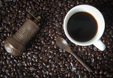 Cup of hot coffee and Turkish coffee grinder lay on coffee bean Royalty Free Stock Photography