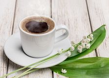Cup of hot coffee and white lilies of the valley. Royalty Free Stock Photography