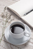 Cup of hot coffee and white note book on white wood table for happy time Royalty Free Stock Image