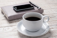 Cup of hot coffee and white note book on wood table Stock Photo