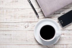 Cup of hot coffee and white note book on wood table Royalty Free Stock Images