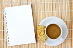 Cup of hot coffee and white sketch book on a mat. White cup of hot coffee and white sketch book on a mat Stock Images