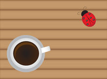 Cup of hot coffee on wood table with cute ladybug Stock Photography