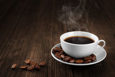 Cup of hot coffee on a wooden table. Coffee beans. Stock Images