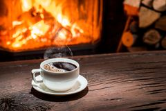 Cup of hot coffee on the wooden table and fireplace at the backg. Round Stock Photo