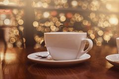 Cup of hot coffee on the wooden table in a coffee shop, blur background with beautiful bokeh effect royalty free stock photos