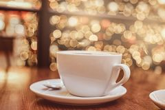 Cup of hot coffee on the wooden table in a coffee shop, blur background with beautiful bokeh effect stock photo
