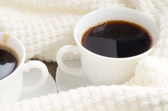Cup with hot coffee wrapped in a white woolen scarf Royalty Free Stock Photos