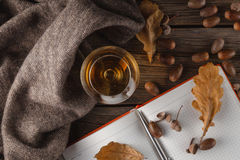 Cup of hot dark coffee and scarf with vibrant autumn leaves on r Stock Photo
