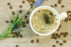 Cup of hot drink with coffee beam and lavender flower on wooden table Royalty Free Stock Images