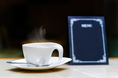 A cup of hot drink. With a menu sign in the background Royalty Free Stock Photos