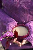 Cup of hot drink in female hands. On warm sweater Stock Photo