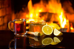 Cup of hot drink with fireplace on background Royalty Free Stock Image