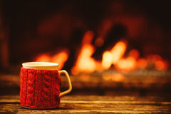 Cup of hot drink in front of warm fireplace. Holiday Christmas c. Oncept. Mug in red knitted mitten standing near fireside. Cozy relaxed magical atmosphere in a Stock Photos