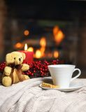 Cup of hot drink teddy bear candle in red Christmas decoration on cozy knitted plaid in front of warm fireplace. Holiday Christmas royalty free stock image