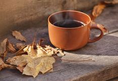 Cup with hot drink on a wooden background autumn Stock Image