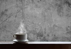 Cup of hot drinks with steam on wood table and concrete background, hot coffee, tea, chocolate and etc. Royalty Free Stock Images