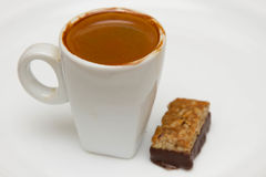 Cup of hot espresso and candy on a white background Stock Photo
