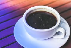 A cup of hot espresso coffee on plate on wooden table in morning rush time with colorful lighting. This will wake you up from sleepiness Stock Photo