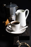 Cup of hot espresso, creamer with milk, cantucci and moka coffee pot on a rustic wooden board Royalty Free Stock Photos