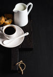 Cup of hot espresso, creamer with milk and cookies on dark rustic wooden board over black background, copy space Stock Photos