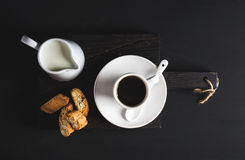 Cup of hot espresso, creamer with milk and cookies on dark rustic wooden board over black background Stock Photos