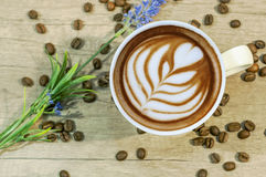 Cup of hot espresso drink with coffee beam and lavender flower o Royalty Free Stock Photography