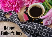 Cup of hot fragrant coffee men`s tie and beautiful flowers stock photo