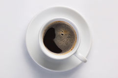 Cup of hot fresh black coffee with foam against white background viewed from top Royalty Free Stock Photography