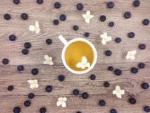 Cup of hot green tea, flowers and berries on wooden table. Flat lay Stock Photography