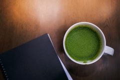 Cup of hot Green Tea Latte and Notebook on the Table in House or Cafe. Top View, Cropped and Closeup shot stock image
