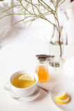 Cup of hot green tea with lemon on white table, fresh lemon and honey - closeup shot. Sun light flair effect. Nice interior in wooden house. Relaxation concept Royalty Free Stock Image