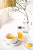 Cup of hot green tea with lemon on white table, fresh lemon and honey - closeup shot. Sun is shining through the window, warm feeling. Relaxation and enjoying Stock Photography