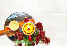 Cup of hot herbal tea, bright colored teapot on wooden tray blackboard, knitted plaid or sweater red chrysanthemum flowers on ligh stock photo