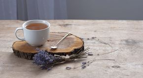 A cup of hot herbal tea and lavender on an old wooden background. Cup of tea Herbal tea Hot drink Vintage texture Background stock photo