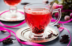Cup of hot hibiscus tea karkade, red sorrel, rosella. Healthy drink from magenta calyces sepals of roselle flowers Royalty Free Stock Photography