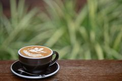 A cup of hot latte art coffee on wood table. royalty free stock photos
