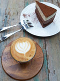 A Cup of hot latte art coffee and delicious chocolate cake. On wooden table stock photos