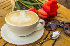 Cup of hot latte art coffee, glasses and tulips on wooden table Royalty Free Stock Photography