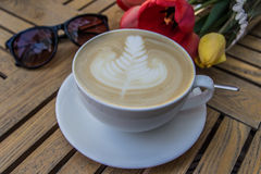 Cup of hot latte art coffee, glasses and tulips on wooden table Royalty Free Stock Photo