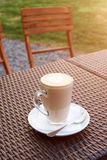 Cup of hot latte art coffee on wicker wooden table in outdoor cafe. Royalty Free Stock Image