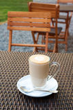 Cup of hot latte art coffee on wicker wooden table in outdoor cafe. Royalty Free Stock Photography