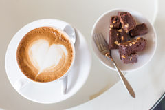 A cup of hot Latte coffee on old wooden table with brownie cake Stock Images