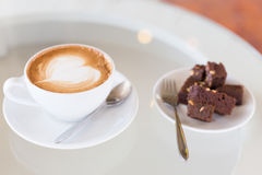 A cup of hot Latte coffee on old wooden table with brownie cake Royalty Free Stock Photo